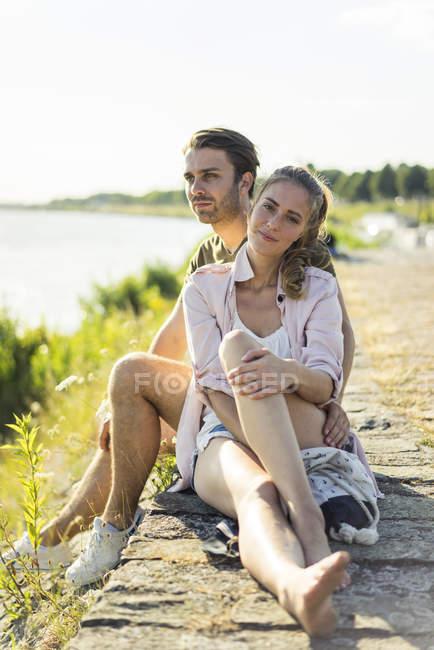Ласковая пара отдыхает на берегу реки летом — стоковое фото