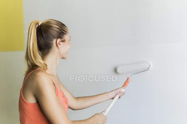 Молодая женщина рисует стену в новом доме — стоковое фото
