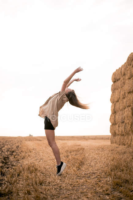 Happy young woman jumping in field — Stock Photo