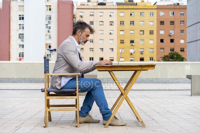 Empresario sentado en la azotea trabajando en el portátil - foto de stock