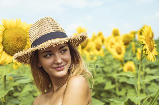Jeune femme avec chapeau de paille souriant dans un champ de tournesols — Photo de stock
