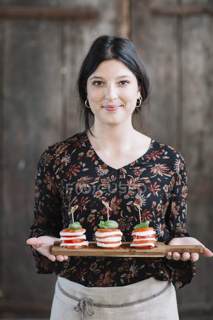 Portrait of smiling woman serving Caprese Salad — Stock Photo