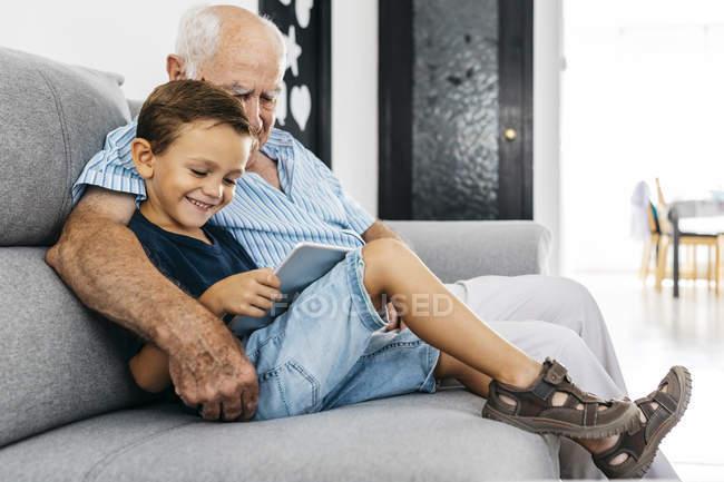 Abuelo y nieto sentados juntos en el sofá en casa y usando una tableta digital - foto de stock