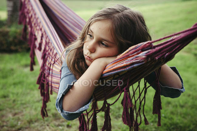 Portrait of sad girl lying in hammock — Stock Photo