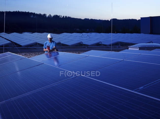 Travailleur avec dispositif de mesure contrôlant l'installation solaire dans la soirée — Photo de stock