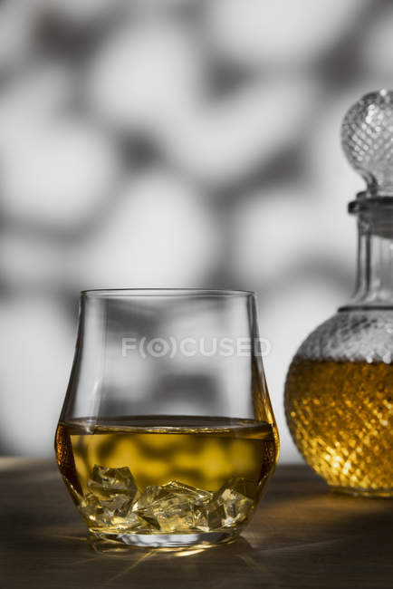 Tumbler with whisky and ice — Stock Photo