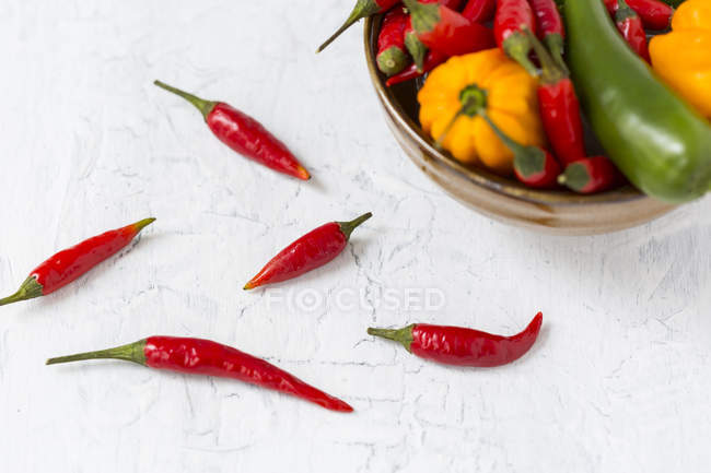 Five red chili pods and bowl of various chili peppers — стокове фото