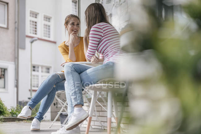 Two girlfriends meeting in a coffee shop, talking — Stock Photo