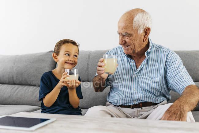 Abuelo y nieto sentados juntos en el sofá y bebiendo limonada - foto de stock