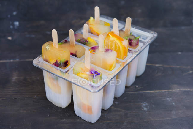 Homemade orange and lemon popsicles with edible flowers — Stock Photo