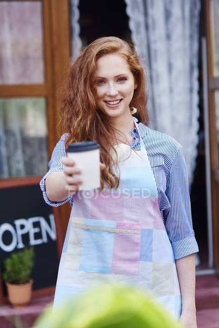 Portrait of smiling waitress offering a coffee — Stock Photo