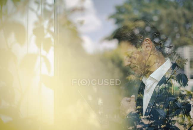 Porträt eines reifen Geschäftsmannes, der am Fenster steht und nach unten schaut — Stockfoto