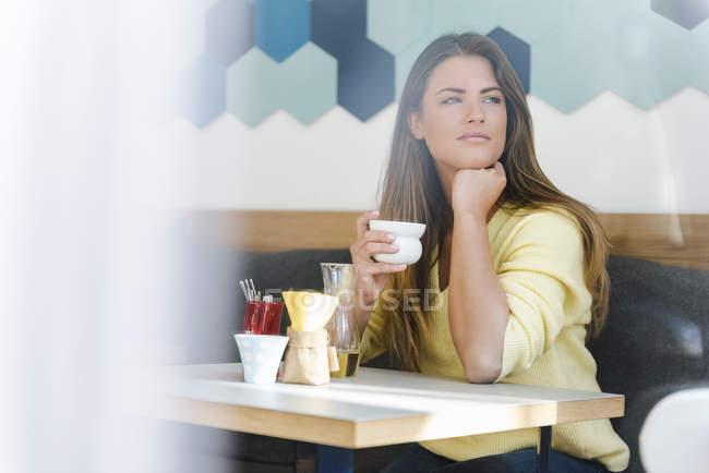 Jeune femme dans un café tenant une tasse de café — Photo de stock