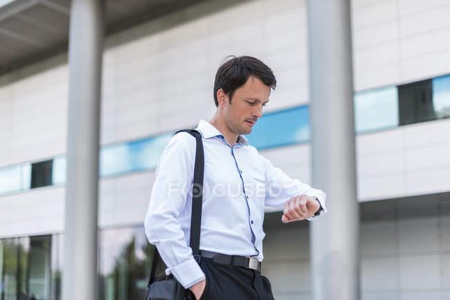 Бизнесмен в городе проверяет время — стоковое фото