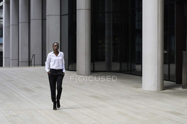 Businesswoman wearing white shirt and black trousers walking in front of modern office building — Stock Photo