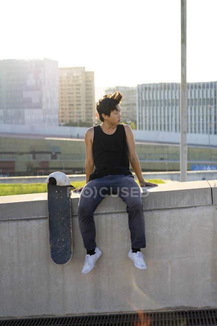 Junger Mann sitzt bei Sonnenuntergang auf Stadtmauer neben Skateboard — Stockfoto