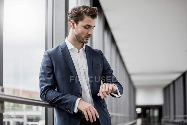 Businessman at the window checking the time — Stock Photo