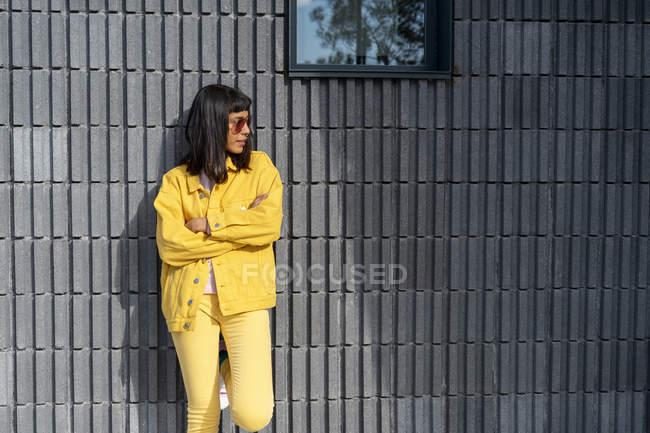 Giovane donna vestita con jeans gialli, distogliendo lo sguardo — Foto stock