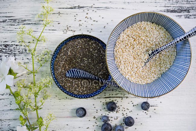 Bowls of black chia seeds and amaranth — Stock Photo