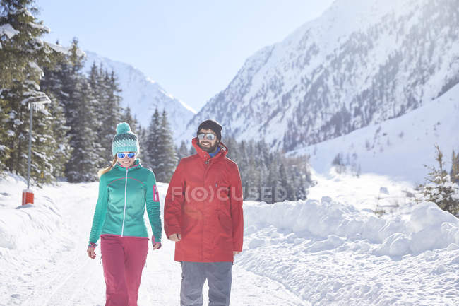 Couple walking in snow-covered landscape - foto de stock