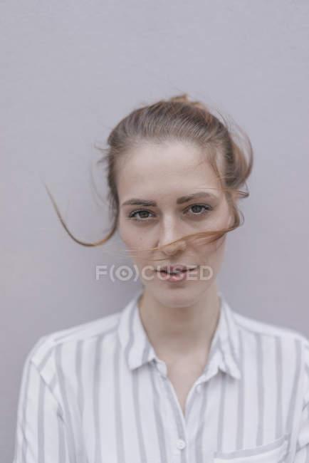 Porträt einer hübschen Frau mit windgewehten Haaren auf grauem Hintergrund — Stockfoto