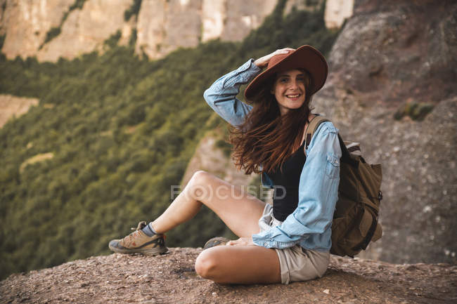 Smiling young woman on a hiking trip wearing a hat sitting on a rock — Stock Photo