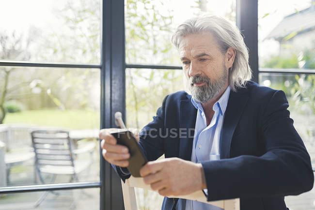 Empresário sênior sentado na cadeira, usando smartphone — Fotografia de Stock