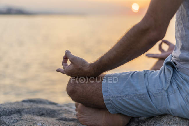 Spain. Man meditating during sunrise on rocky beach, mudra — стоковое фото