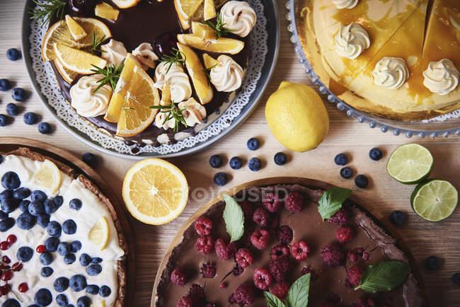 Pasteles sabrosos con bayas en la mesa - foto de stock