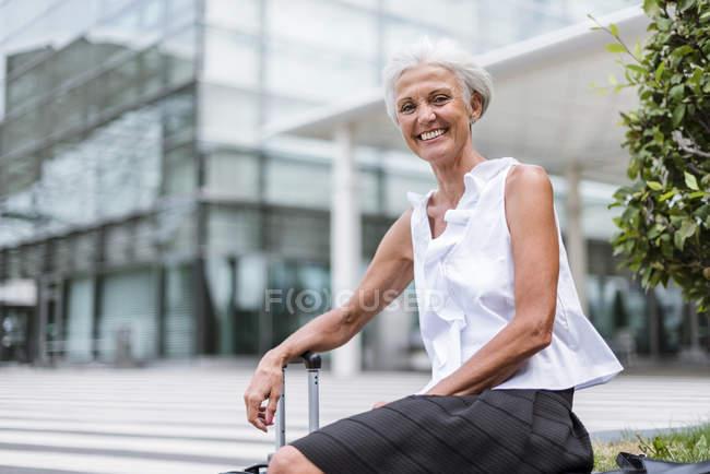 Портрет щаслива старша жінка з багажем сидячи в місті — стокове фото