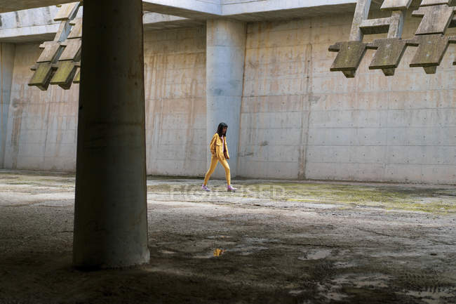 Young woman wearing yellow jeans clothes, walking — Stock Photo