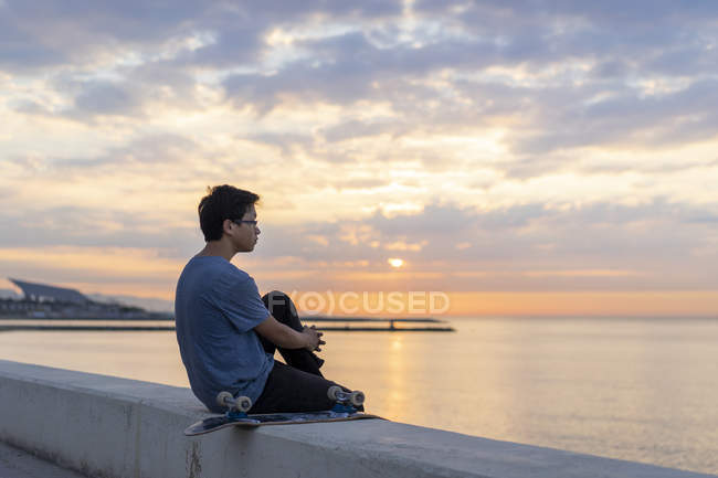 Young Chinese man with skateboard sitting on wall at the beach — Stock Photo