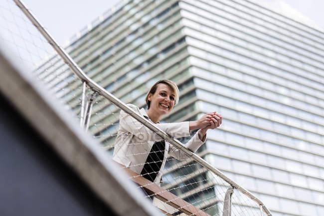 Lächelnde Geschäftsfrau lehnt an Geländer — Stockfoto