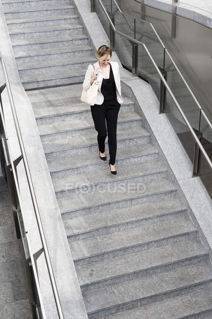 Selbstbewusste Geschäftsfrau läuft in der Stadt die Treppe hinunter — Stockfoto