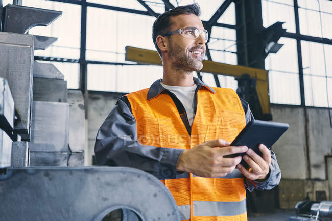 Smiling man with tablet wearing protective workwear in factory — Stock Photo