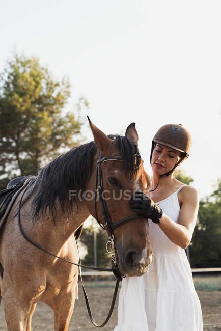 Портрет женщины в платье и шлеме, гладящей лошадь на улице — стоковое фото