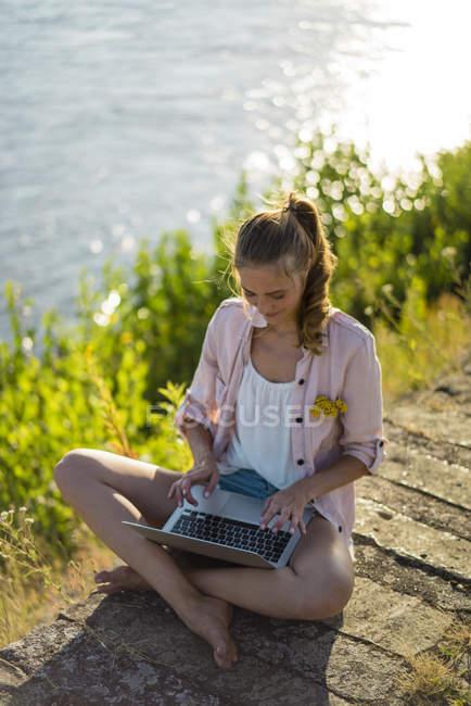 Woman sitting at riverside in summer using laptop — Stock Photo
