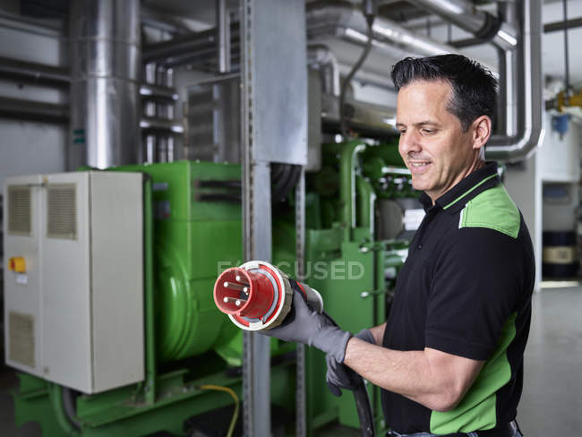 Combined heat and power plant, worker holding high current plug — Stock Photo