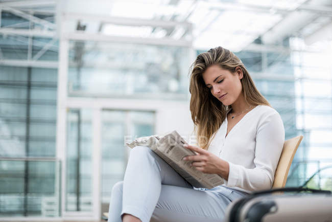 Young businesswoman sitting outdoors with suitcase reading newspaper — Stock Photo