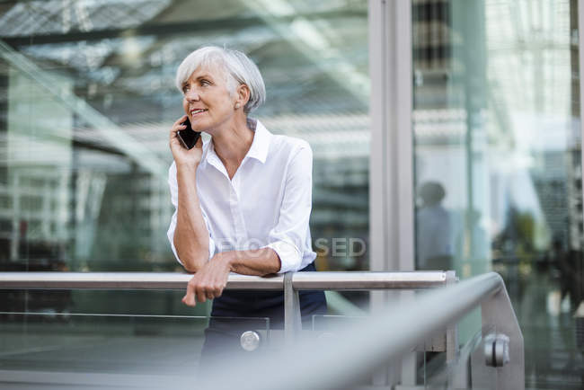 Senior businesswoman leaning on railing in city and talking on cell phone — Stock Photo