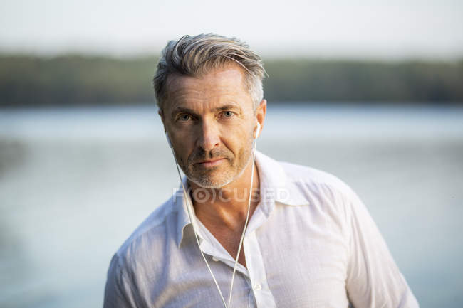Portrait of man listening music with earphones at lake — Stock Photo