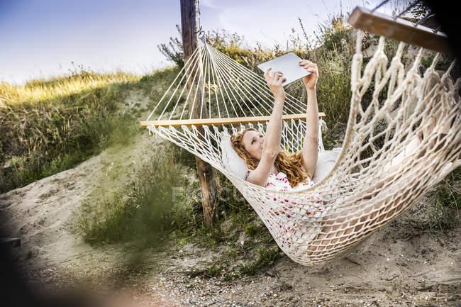 Женщина лежит в гамаке и делает селфи с планшетом. — стоковое фото