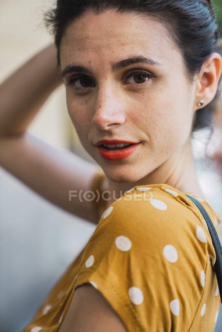 Portrait of woman wearing yellow dress with polka dots — Stock Photo