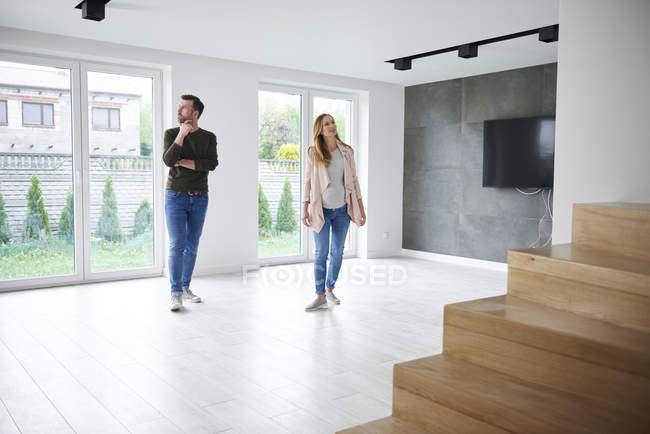 Casal olhando ao redor em apartamento vazio — Fotografia de Stock
