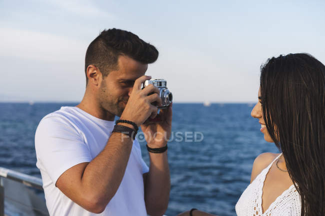 Young romantic couple taking photos at sea — Stock Photo