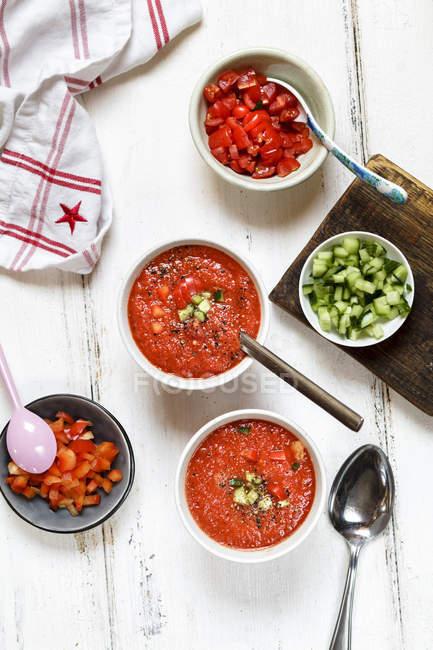 Deux bols de Gazpacho et des bols d'ingrédients — Photo de stock