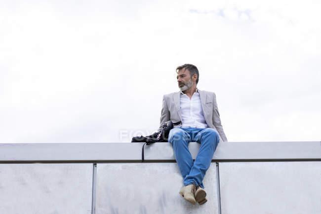 Повсякденний бізнесмен, сидячи на стіні — стокове фото