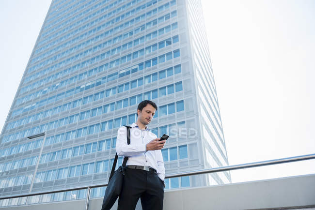 Businessman using cell phone in the city — Stock Photo