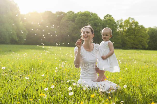 Мать и дочь с мячом на лугу летом — стоковое фото