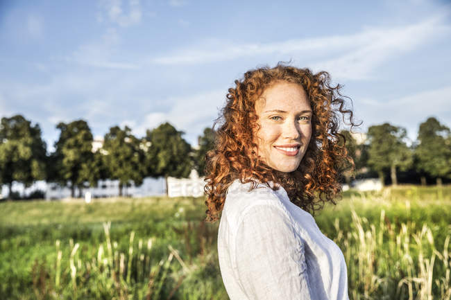 Portrait of smiling young woman with curly red hair posing in nature — Stock Photo